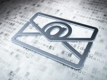Ein silberner Briefumschlag mit dem E-Mail-@-Zeichen liegt auf einem Dokument